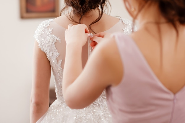 Bridesmaid helping bride fasten corset and getting her dress, preparing bride in morning for the wedding day. bride's meeting.