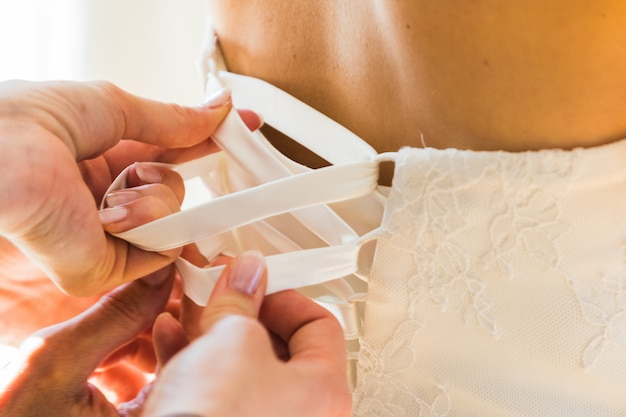 Bridesmaid helping bride fasten corset and getting her dress, preparing bride in morning for the wedding day