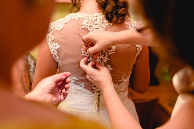 Bridesmaid helps the bride to get dressed on her wedding day