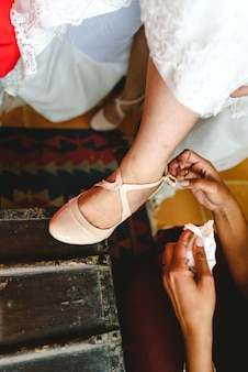 Bridesmaid helps the bride to put on her shoes.