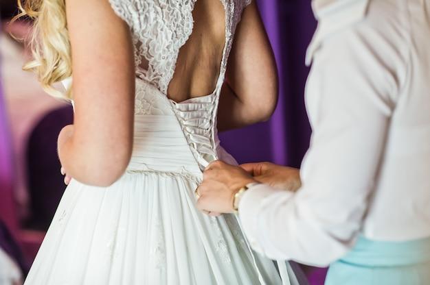 Bridesmaid helps to dress the bride wedding dress, hotel interior, purple background