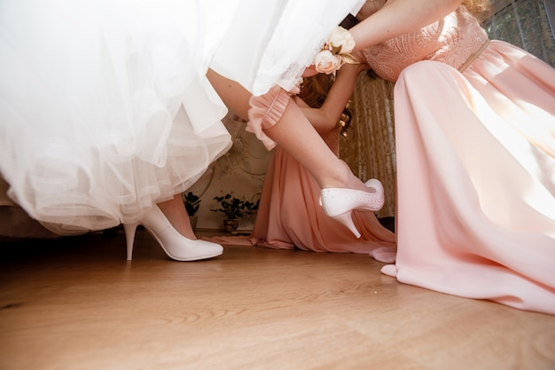 The bridesmaid helps her to wear a dressing-jewelry on her leg.
