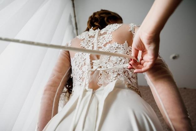 Bridesmaid helps to tie ribbon on white elegant wedding dress