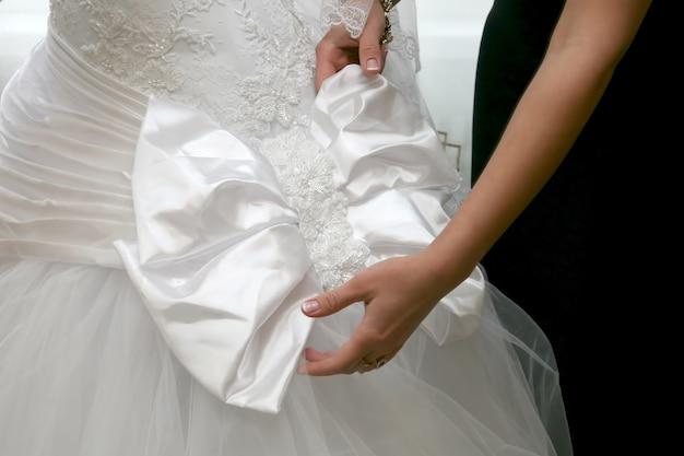 신부 들러리는 신부 드레스의 활을 교정하는 데 도움을 줍니다. 여성복의 아름다움과 패션