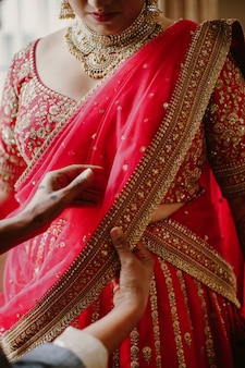 Bridesmaid helps to wear the traditional indian bride dress