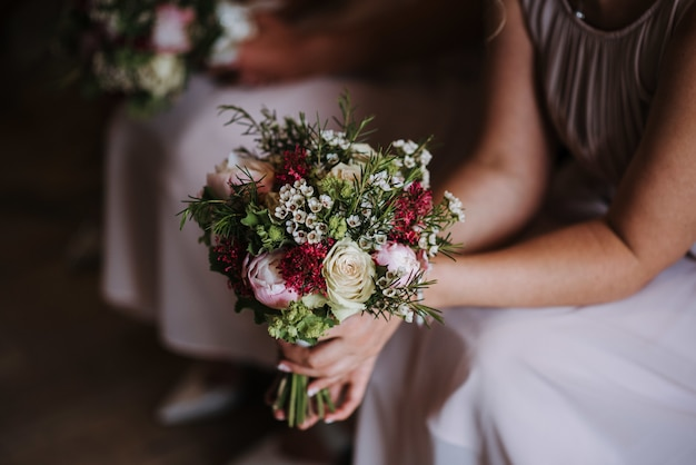 Bridesmaid holding the wedding day's beautiful bouquet of roses