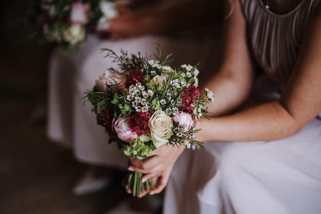 Damigella d'onore che tiene il bellissimo mazzo di rose del giorno del matrimonio