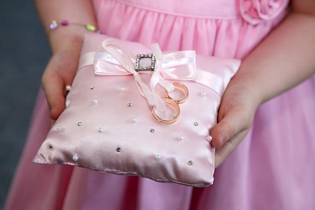 신부 들러리는 결혼 금 반지와 함께 장식 쿠션을 보유