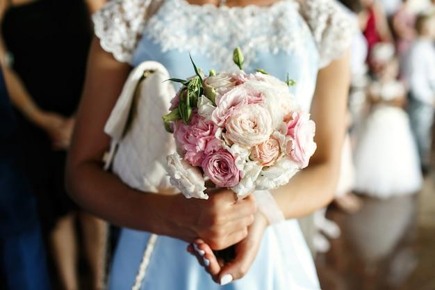 青いドレスの花嫁介添人がピンクの結婚式の花束を保持