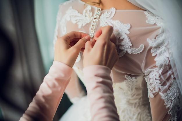 Подружка невесты делает бант на спине свадебного платья невесты