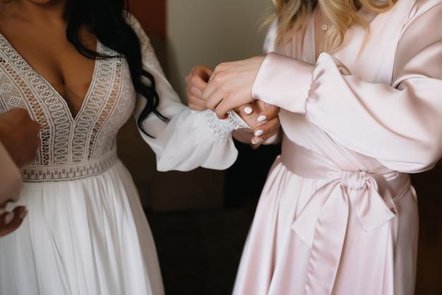 Bridesmaid preparing bride for wedding day