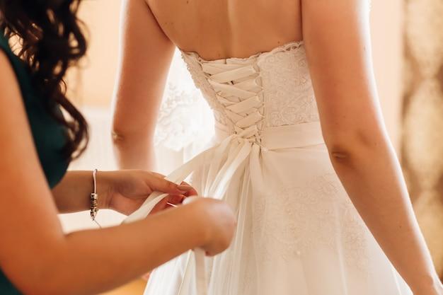 Подружка невесты завязывает бант на корсете свадебного платья крупным планом