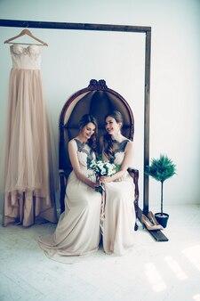 Подружка невесты со свадебным букетом, сидя в винтажном кресле. фото с копией пространства
