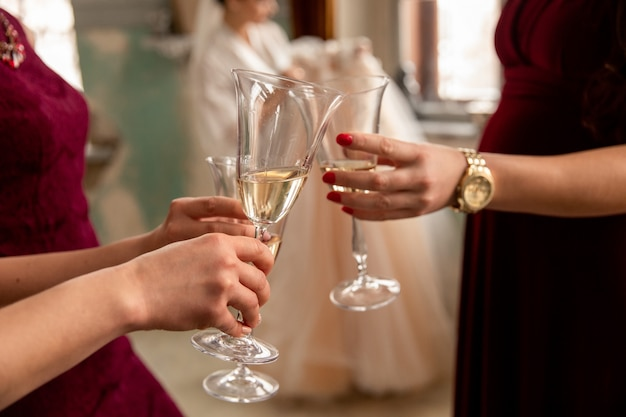 Bridesmaids clink glasses with champagne on bride with wedding dress