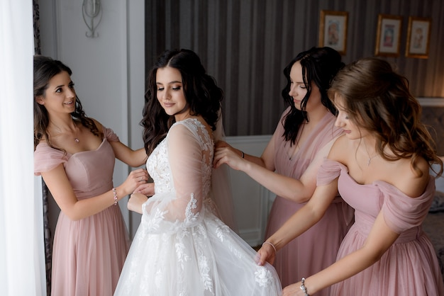 Bridesmaids dressed in pink dresses are helping bride to prepare for the wedding ceremony
