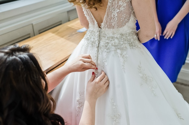 Bridesmaids help the bride to wear a wedding dress