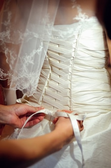 Подружки невесты помогают невесте надеть свадебное платье.