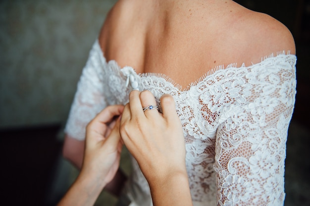 Bridesmaids helping to wear a wedding lace dress