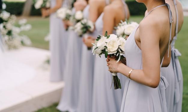 ドレスを着た花嫁介添人は、花束を一列に並べて立っています