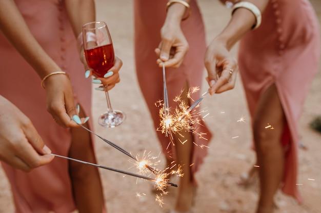 Подружки невесты в красивых платьях празднуют свадьбу на открытом воздухе