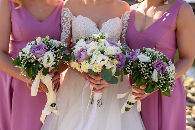 Bridesmaids in pink dresses and the bride are holding their bouquets. close-up.