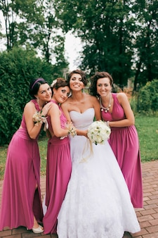 Bridesmaids in pink dresses hug the bride and laugh at an italian wedding.