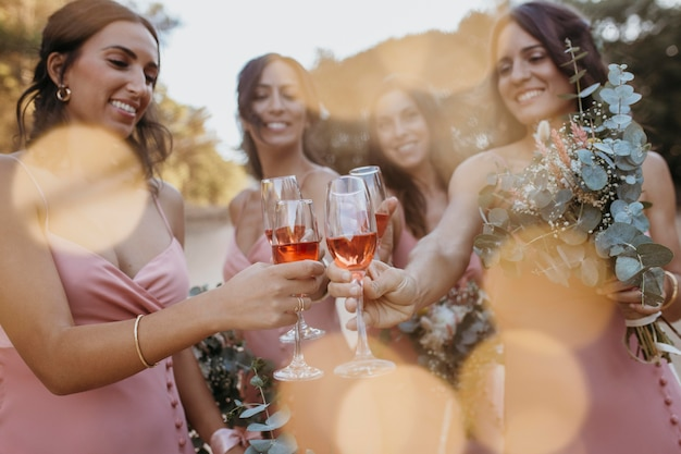 Bridesmaids in pretty dresses celebrating the wedding outdoors