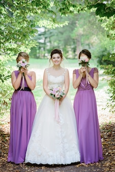Bridesmaids in violet dresses hide their faces behind bouquets standing with bride