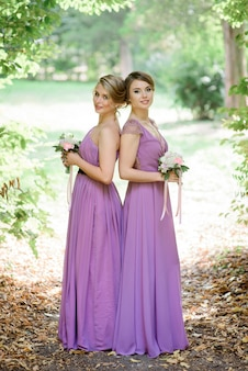 Bridesmaids in violet dresses stand side by side under arch of green branches
