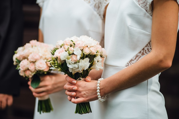 Bridesmaids in white dresses are holding bouquets of roses