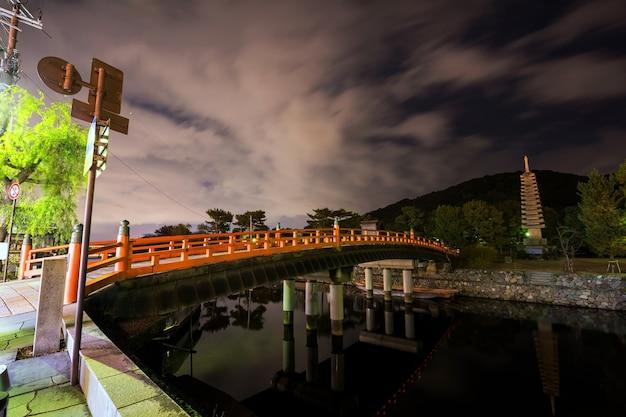 京都府宇治市の夜の運河と13階建ての石塔を渡る橋