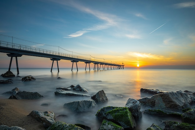 Bridge on the beach at sunrise