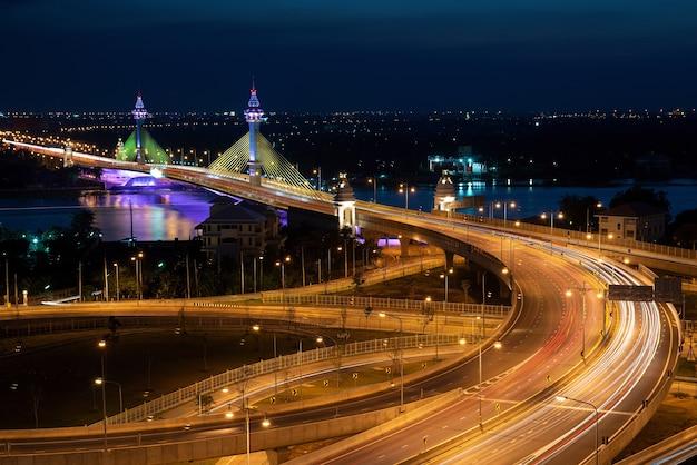 Мост, пересекающий свет шоссе ночью.