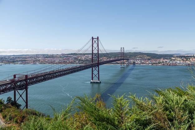 Мост в лиссабоне через реку тежу с движущимися автомобилями.