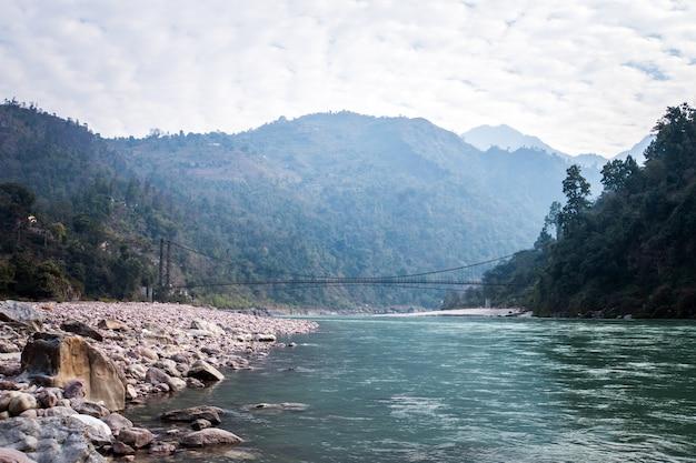 リシケシインドの近くの橋。川に架かる吊橋。長いロープのつり橋が村の小川を渡る