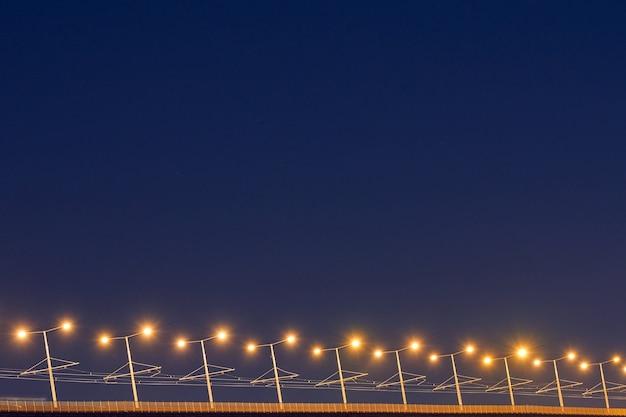 Мостовые столбы ночью. красивый желтый свет дорожных столбов. минимальная ночная фотография, копия пространства