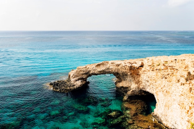 Bridge of lovers rock formation on the rocky shore of the mediterranean sea on the island of cyprus ayia napa. no people.