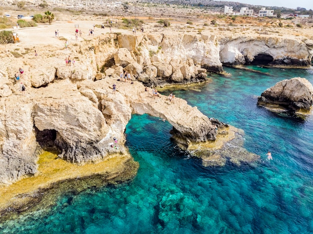 Bridge of lovers rock formation on the rocky shore of the mediterranean sea on the island of cyprus ayia napa. tourists walk along the shore. coral and stone coast, turquoise water in the sea.