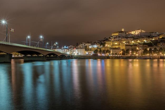 Мост на море в коимбре с огнями, отражающимися в воде ночью в португалии