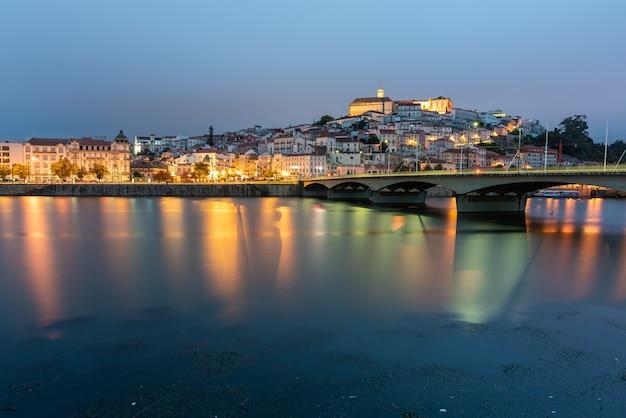 Мост на море в окружении коимбры с отражающимися огнями в воде в португалии