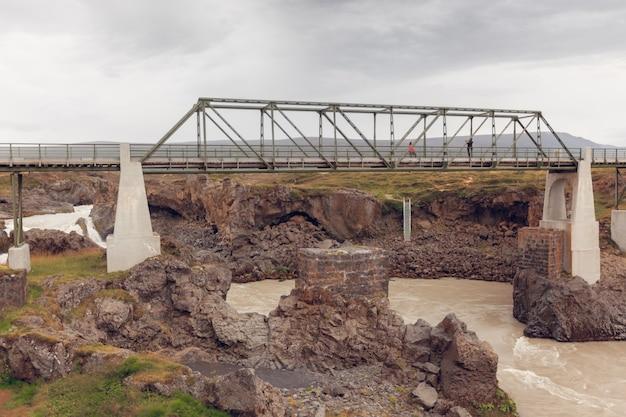 Мост через реку скьялфандафлёт в исландии. пасмурная пасмурная погода