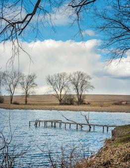 이른 봄에 작은 호수 기슭에 교각과 나무