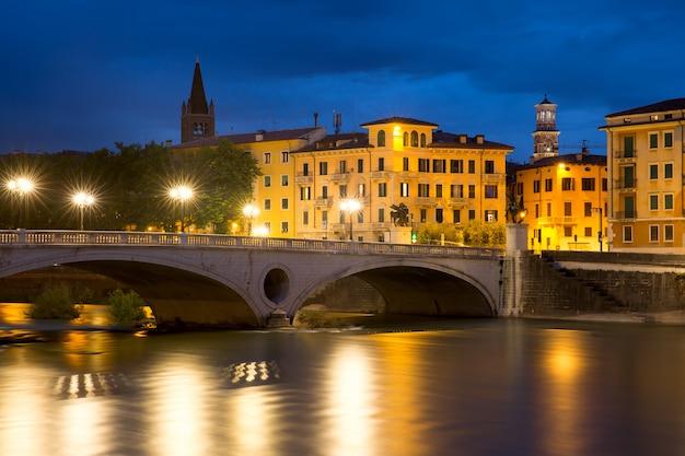 Bridge ponte risorgimento and the river adige at night illumination in verona, italy