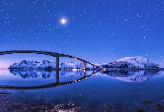 Bridge and purple starry sky with beautiful reflection in water