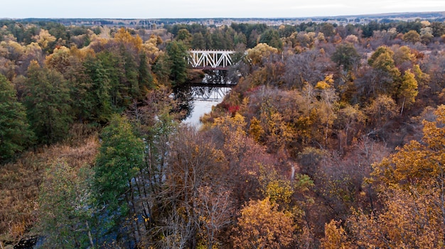 Bridge over a river between reserved autumn forests along which the railway passes.