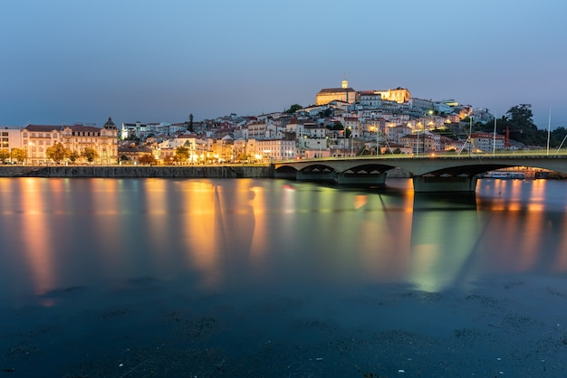 Bridge on the sea surrounded by coimbra with the lights reflecting on the water in portugal