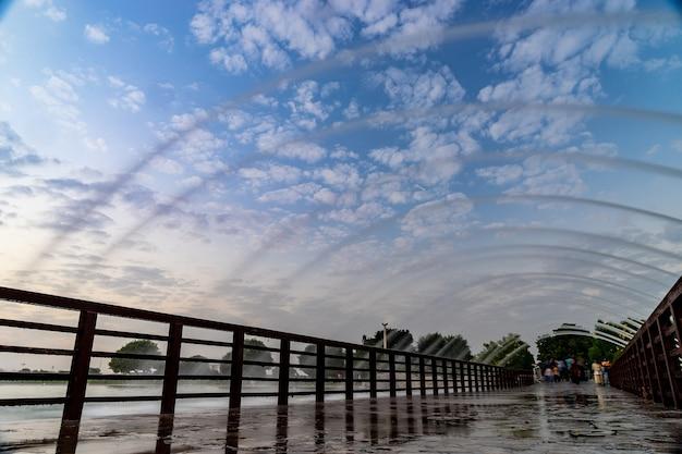 Мост с фонтаном в парке aspire во время драматического заката в дохе, катар.