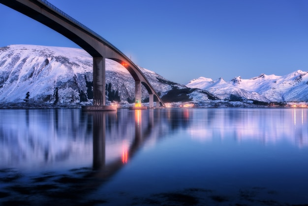 Bridge with illumination, snow covered mountains, village and blue sky with beautiful reflection in water
