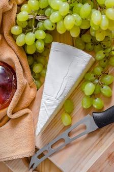 木の板にブリーチーズと白の新鮮なブドウ