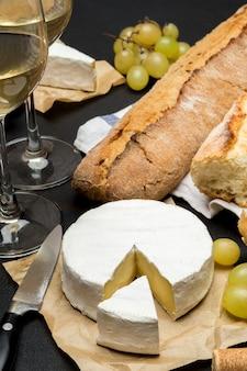 ブリーチーズ、バゲット、暗いコンクリートの背景に白ワインを2杯